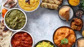 curry : Assorted indian food on stone background. Dishes of indian cuisine. Tikka masala, butter chicken, Nilgiri, seekh kebab, rice, Onion Bhajia, paneer, samosa, naan, Daal Tarka, spices With copy space