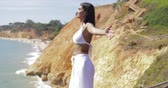 Wonderful fit brunette in white outfit posing with eyes closed enjoying sunshine and fresh air of ocean on background of cliffs.