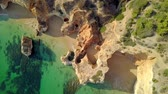 quadcopter : From above aerial view of rough cliffs on shoreline of tropical ocean with green water washing white sands in lagoon, Portugal, Algarve. Stock Footage