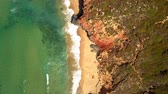 From above aerial shot of ocean clear water washing rocky and sandy beach of tropical coastline in Algarve, Portugal.