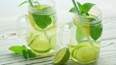 citrus fruit recipes : Few glass jar cups with green straws and fresh lemonade with lime slices and green mint served on wooden table