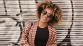 Portrait of contemporary young ethnic woman with Afro hairstyle wearing sunglasses and smiling happily at camera standing against street wall with graffiti