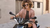 beira da estrada : Stylish modern black woman with Afro hair and in sunglasses and sitting on moped on street looking confidently at camera Stock Footage