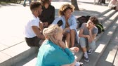 Group of modern stylish multiracial men and women gathering on steps on street having fun and chatting in summer sunlight