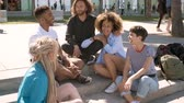 ırklı : Group of young multiracial men and women sitting on pavement steps in summertime chatting and spending time happily in leisure Stok Video