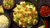 халапеньо : Tasty mexican nachos chips served on ceramic plate with cheese, hot peppers, tomatoes, limes, salsa and guacamole. Placed on dark rusty table. Стоковые видеозаписи