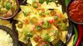 mexikanisch : Fresh yellow corn nacho chips garnished with melted cheese, peppers and tomatoes in a handmade ceramic plate on rusty table