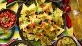 cheese sauce : Mexican nachos tortilla chips with black bean, jalapeno, guacamole, tomatoes salsa, cheese and botteled beer. Placed on a table. Stock Footage