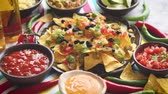 çili : Mexican corn nacho spicy chips served with melted cheese, peppers, tomatoes, beer and side salsas. Stok Video