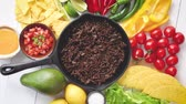 taco : Chili con carne in frying pan on white wooden table. Ingredients for making Chili con carne.Top view. Chili with meat, nachos, tacos, limes, avocado, hot pepper. Mexican Texas traditional dish