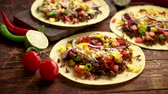burrito : Healthy corn tortillas with grilled beef, fresh hot peppers, cheese, tomatoes over rusty wooden table background, top view, copy space. Mexican food contept.