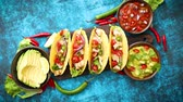 molho de carne : Mexican taco with chicken meat, jalapeno, fresh vegetables served with guacamole and tomato salsa. Latin american food. Placed on blue table.