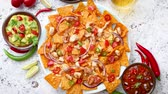 халапеньо : A plate of delicious tortilla nachos with melted cheese sauce, grilled chicken, jalapeno peppers, red onion, tomato, guacamole dip and spicy salsa. With cold sparkling beer.