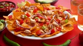 çili : A plate of delicious tortilla nachos with melted cheese sauce, grilled chicken, jalapeno peppers, red onion, tomato, guacamole dip and spicy salsa. With cold sparkling beer. Placed on red background