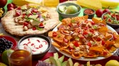 çili : An overhead photo of an assortment of many different Mexican foods, including tacos, guacamole, nachos with grilled chicken, tortillas, salsas and others Stok Video