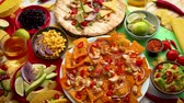 çili : Various freshly made Mexican foods assortment. Placed on colorful table. With nachos, tacos, tortillas, grilled meat, dips, salsa and vegetables.