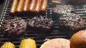 rôti de porc : Mixed american barbecue food on hot grill. Hamburgers, hotdogs, corn being grilled. Tasty composition. Outdoor party.