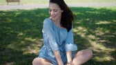 Portrait of attractive brunette woman in blue dress sitting in a park on the grass at sunny warm day. She enjoy summer and relaxing outdoor. Stock Footage