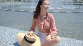 Beautiful woman posing next to city fountain in summer time. She wearing straw hat and smiling and looking to camera.