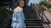 Beautiful woman in summer fashion dress walking on stairs in the middle of city. Smiling to the camera.
