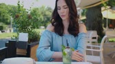 Beauiful woman sitting in outdoor restaurant and sip mojito dring in summer hot day. Smiling to the camera. Stock Footage