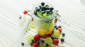 киви : From above shot of jar filled with colorful mix of sweet fruit and berry mix and served on table