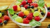 parcela : From above glass bowl with assortment of fruits on light wooden table