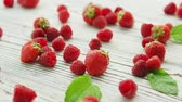 Bunch of fresh strawberries and ripe raspberries lying on surface of white timber tabletop near green leaves Stock Footage