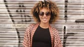 encaracolado : Portrait of contemporary young ethnic woman with Afro hairstyle wearing sunglasses and smiling happily at camera standing against street wall with graffiti