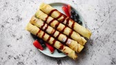 banan : Plate of delicious crepes roll with fresh fruits and chocolate placed on rusty table. Top view, flat lay.