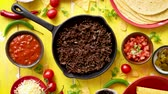 cuochi : Various fresh and tasty ingredients for chilli con carne. With meat on iron pan, tortillas, vegetables, cheese, bean. Placed on wooden yellow table