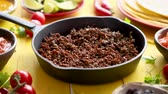 ingredienti : Various fresh and tasty ingredients for chilli con carne. With meat on iron pan, tortillas, vegetables, cheese, bean. Placed on wooden yellow table