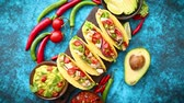 view from above : Mexican taco with chicken meat, jalapeno, fresh vegetables served with guacamole and tomato salsa. Latin american food. Placed on blue table.