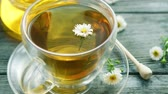 composições : Closeup shot of glass mug on saucer filled with herbal tea and tiny camomile flowers on wooden table with jar of honey