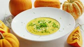 abóbora : From above view of yellow pumpkin soup sprinkled with green herb and surrounded by pumpkins on white table