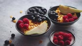 müsli : Healthy breakfast for two is served. Golden cornflakes with fresh fruits of raspberries, blueberries and pear in two ceramic bowls. Placed on stone background. Stok Video