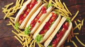 ketçap : American hot dogs assorted in row. Served with french fries. Placed on wooden table. Above view on a rustic wood background Stok Video