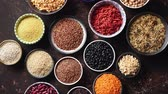 detoks : Various superfoods in smal bowls on dark rusty background. Superfood as rice, lentil, beans, peas, goji, flaxseed, buckwheat, couscous, chickpeas Top view Flat lay