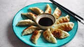 sesamo : Traditional asian dumplings Gyozas on turqoise ceramic hand painted plate served with chopsticks and bowl of soy sauce over concrete texture background. Top view with copy space.