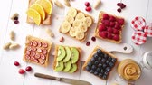 vaj : Assortment of healthy fresh breakfast toasts. Bread slices with peanut butter and various fruits and ingredients on side. Placed on white wooden table. Top view, with copy space.