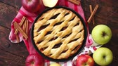 ingredienti : Traditional american apple pie served with fresh fruits, cinnamon sticks in a black ceramic plate. Flat lay and top view on rusty wooden table.
