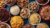 kukoricapehely : Assortment of various kinds cereals placed in ceramic bowls with cornflakes, granola, cereals and oatmeal. Flat lay, top view on blue rusty table with copy space in the middle Stock mozgókép