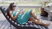 odpoczynek : Charming young long haired female in sunglasses wearing blue dress laying on chaise lounge and using smartphone