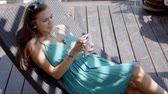 view from above : From above of pretty young brunette with eyeglasses on head wearing blue strap dress reading message on smartphone. while enjoying sunny day and laying on lounge chair with wooden floor on background