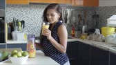 džbán : Brown haired woman smiling dreamily while tasting fresh orange juice from glass standing in front of kitchen counter in daylight