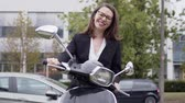 Confident elegant female in black suit and glasses sitting on motorbike against city street with cars and office building smiling brightly at camera Stock Footage