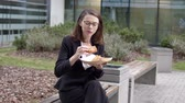 Enthusiastic smart woman in official suit sitting on bench and eating sandwich from plate in hand in square of business center