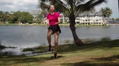 Young sportive female doing exercise with raised bent knee during morning workout in calm place at tropical lake