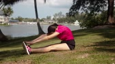 Side view of healthy young woman sitting on grass and leaning forward while doing stretching exercises during morning training by lake