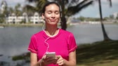 Young female in pink shirt choosing playlist on smartphone while listening to music with earphones during morning walking on tropical lakeside